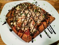 Pretzel Flatbread with Charred tomato, Goat Cheese, and Balsamic Syrup ($8).